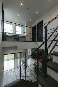 二層吹抜の階段スペースから、LDKと2階を望む。光をもたらし、気配を届かせ、開放感と心地よさを創ります。