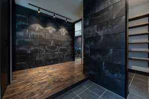 外壁と同じセメントウォールが、高級感を演出するエントランス。右の開口からDKへと繋がります。