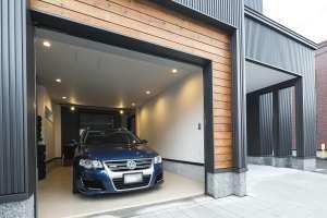 ガレージの入口には木のアクセント。カーポートと石畳のアウトサイド一体を使って、楽しめる家