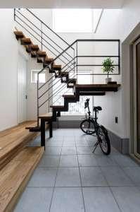 吹抜けのエントランス。スチールバーのスケルトン階段が光を通し、土間に広がる美しい空間