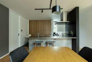 ステンレスの一枚板が美しいアイランドキッチン。左の白い扉はパントリーへの入口