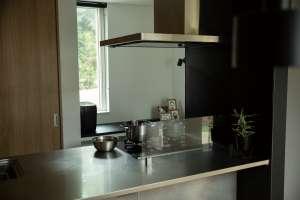 ステンレスがカウンターテーブルにもなるキッチン。ブラックのパーテーションはマグネットボードになっています。