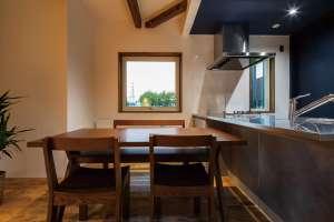 木枠で囲った窓。オープンなキッチンは美しいステンレスで演出。