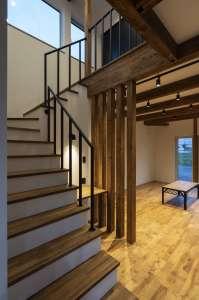 スチールバーの階段と木の列柱、2階の気配を通す階段